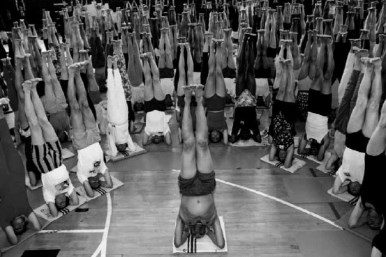 Iyengar practicing head balance (in 1993, at age 75) with students.